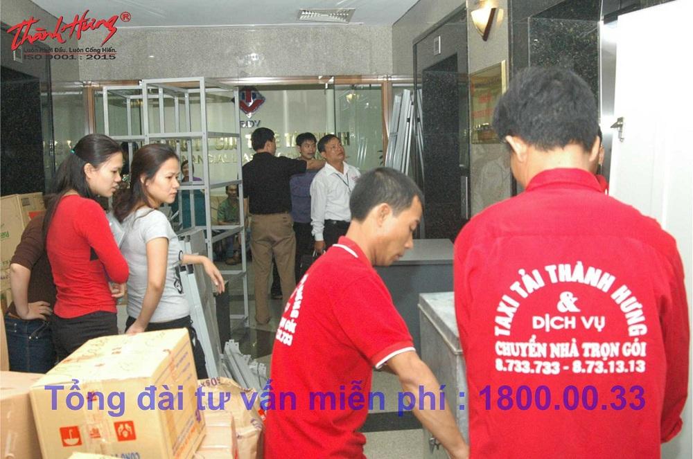 Nhân viên công ty đang đóng gói hàng hóa của khách hàng để chuẩn bị đưa lên xe tải.
